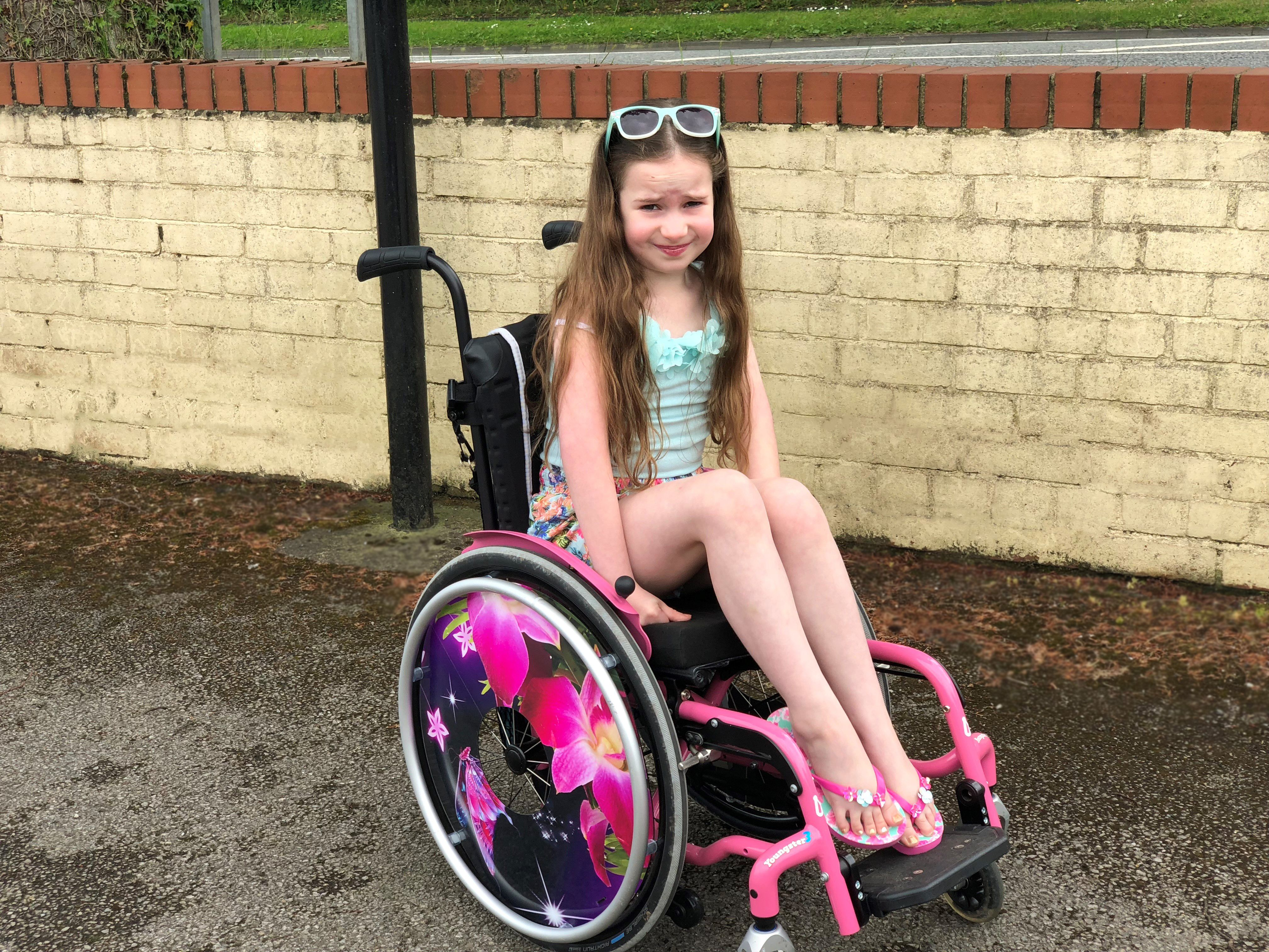 Amelia sat in the Zippie Youngster 3 wheelchair with flowery spoke covers on the wheels