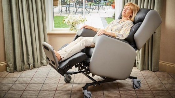 A lady sat in a Lento care chair - one of the best seating for kyphosis
