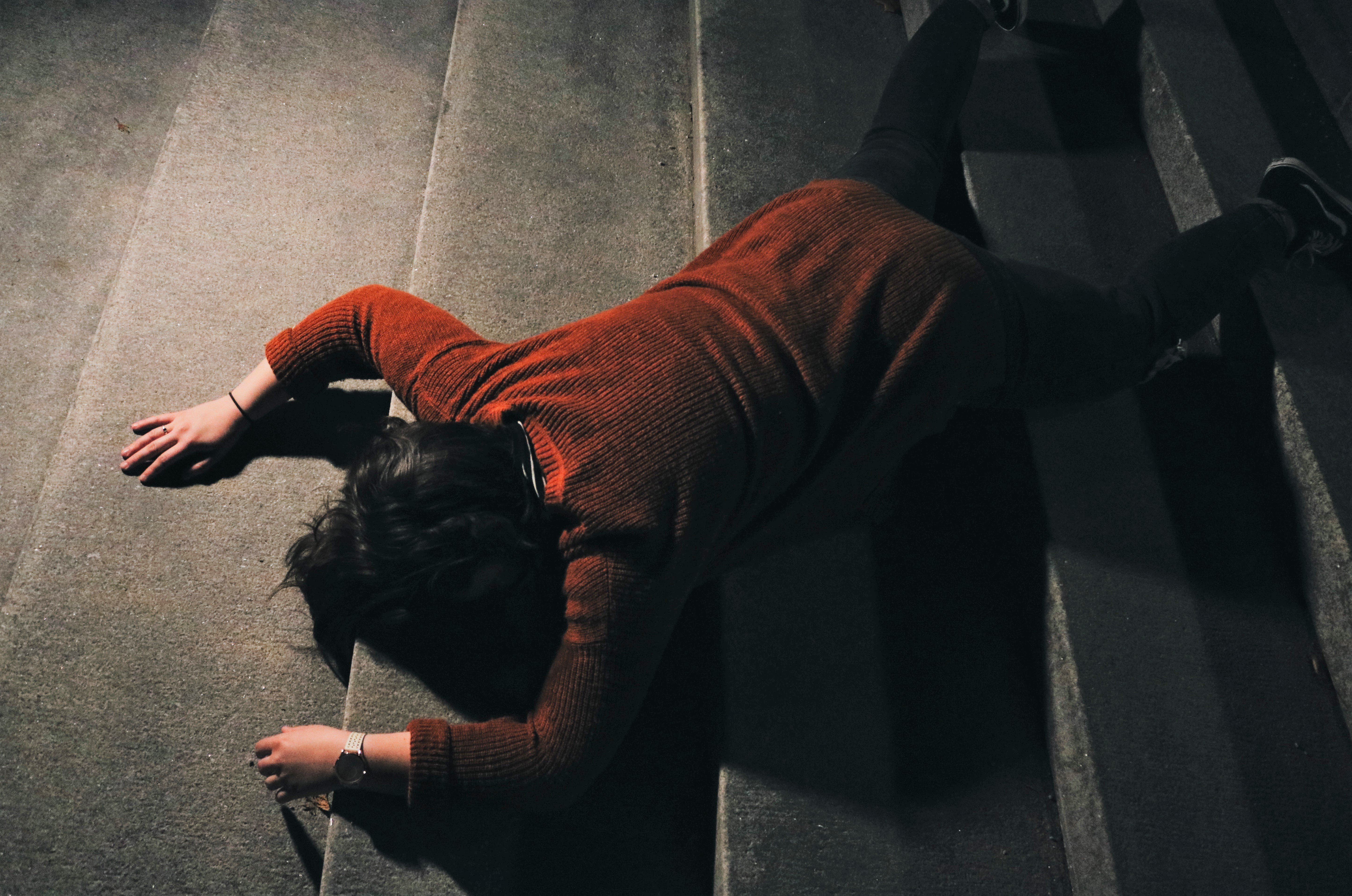 A woman fallen over on the floor face down.