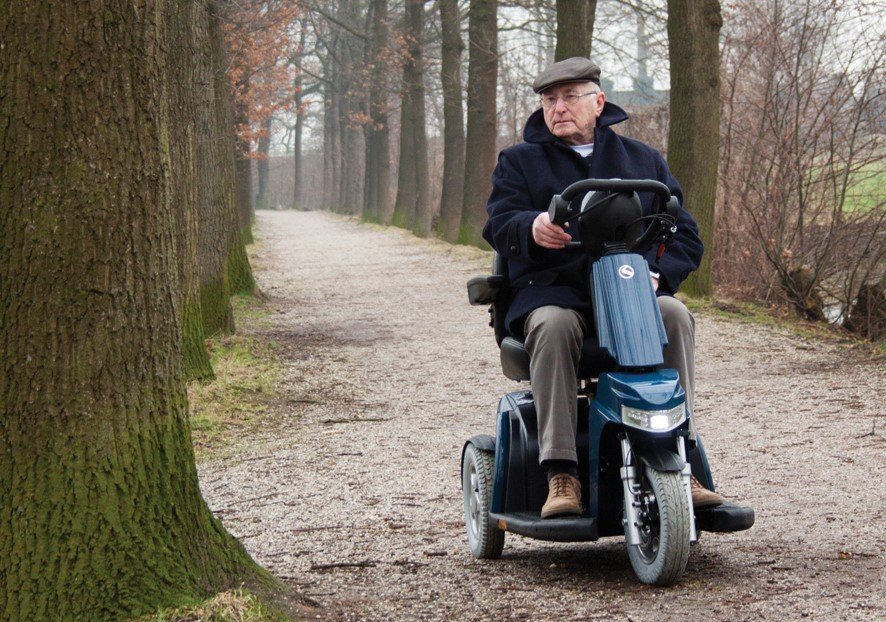 A man driving a mobility scooter through the woods.